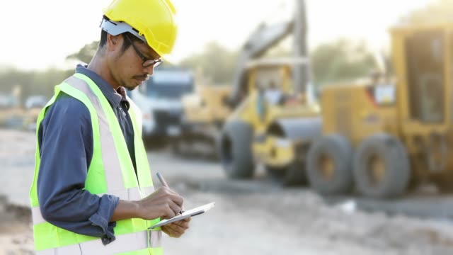 asian engineer with hardhat using  tablet pc computer inspecting and working at construction site - agricultural equipment stock videos and b-roll footage