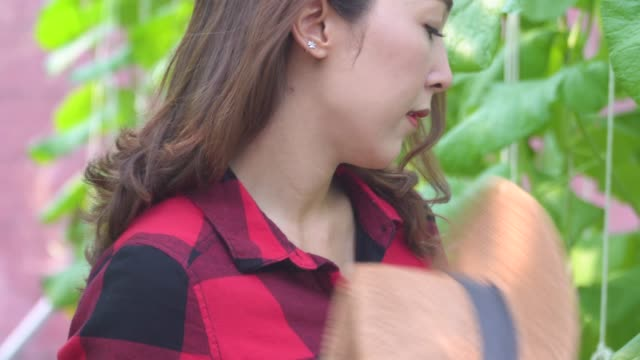 Asian exhausted young woman suffers from heat in greenhouse