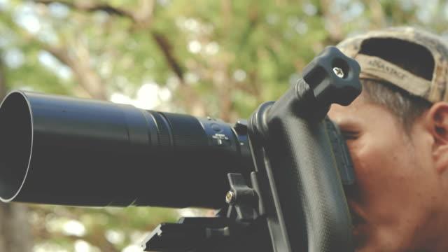 vídeos de stock, filmes e b-roll de fotógrafo de explorador asiáticos é tirar fotografias em uma floresta - jornalista