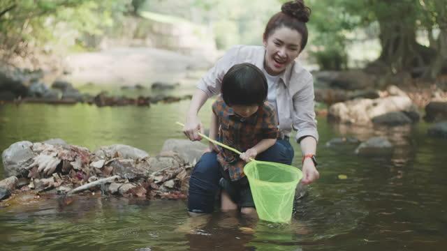 famiglia asiatica e due figli che pescano con rete da pesca nel fiume - camminare nell'acqua video stock e b–roll