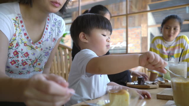 asian family at a bakery shop enjoying a delicious cake together - guest stock videos & royalty-free footage