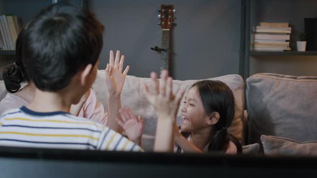 vídeos y material grabado en eventos de stock de familia asiática hermano y hermana viendo deporte en la televisión y feliz emocionado en casa en la noche - exclusivamente japonés