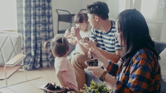 asian family celebrating birthday and eating cake in the living room (slow motion) - dessert stock videos & royalty-free footage