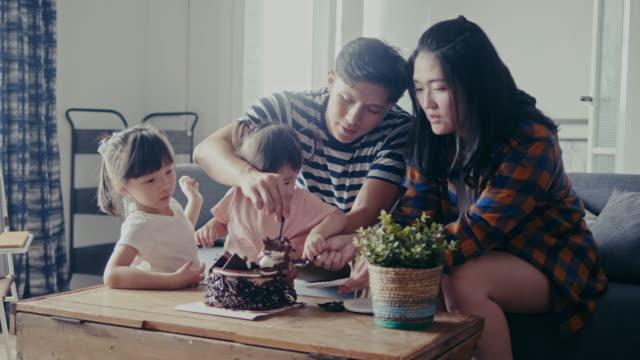 vídeos de stock, filmes e b-roll de família asiática que comemora o aniversário e que come o bolo na sala de visitas (movimento lento) - família jovem