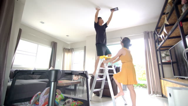 asian family changing light bulb together in the living room - changing lightbulb stock videos & royalty-free footage