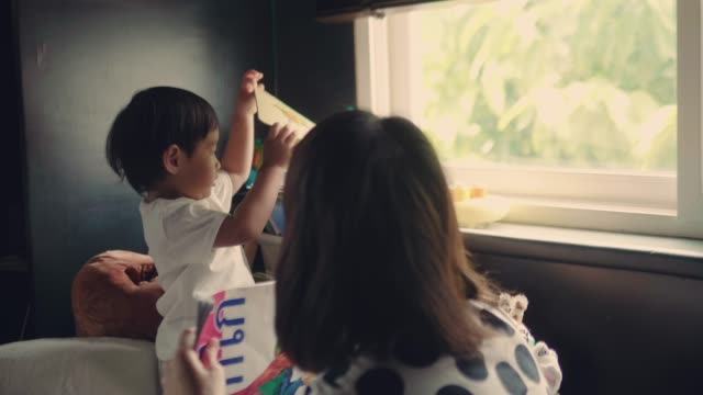 asian family choosing book on bookshelf. - stack stock videos and b-roll footage