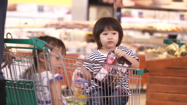 vídeos y material grabado en eventos de stock de familia asiática de niño y niña en el carro de compras con sus padres son compras en las tiendas de comestibles - carrito de la compra