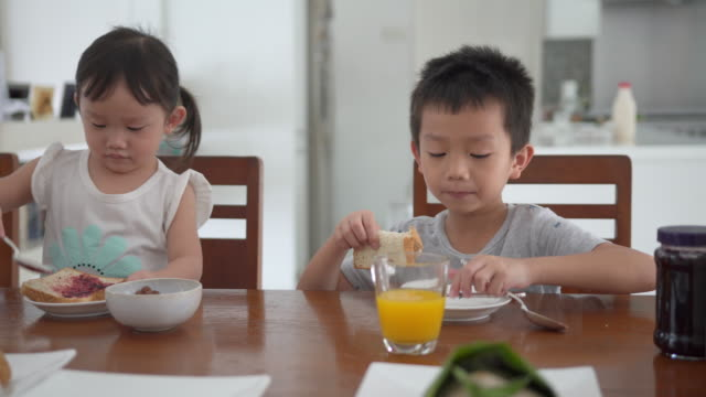Asian family eating breakfast and enjoying family time