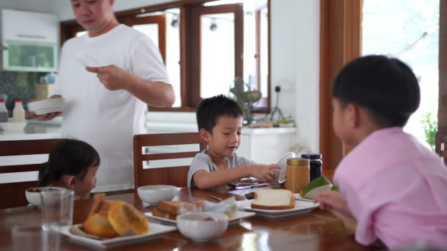 asian family eating breakfast in domestic kitchen - chinese ethnicity stock videos and b-roll footage