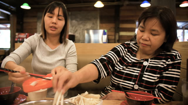asian family eating shabu shabu - macchina da presa manuale video stock e b–roll