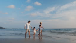 Asian family happy travel on the beach summer together in holiday. Father, mother and children walking together. Concept of family, travel and relation. 4k resolution.