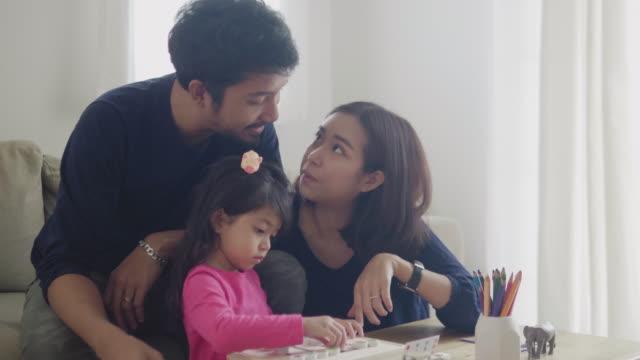 アジアの家族は楽しみを持っており、自宅で木製のおもちゃを再生しています - 両親点の映像素材/bロール