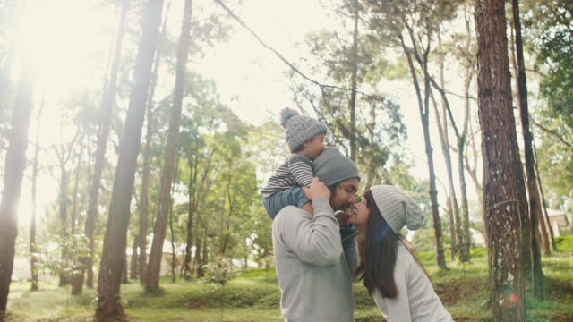 asian family having fun together in the forest at sunset. - woolly hat stock videos and b-roll footage