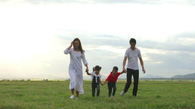 asiatische familie hält ballon und zu fuß auf der wiese bei sonnenuntergang - gemeinsam gehen stock-videos und b-roll-filmmaterial