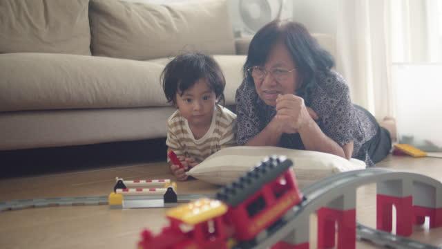アジアの家族は、リビングルームで一緒に鉄道線路を構築しています。 - 大家族点の映像素材/bロール