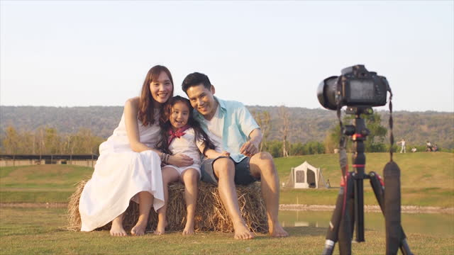 asian family is using a camera on a tripod to take photos of their family while on vacation. - digital camera stock videos & royalty-free footage