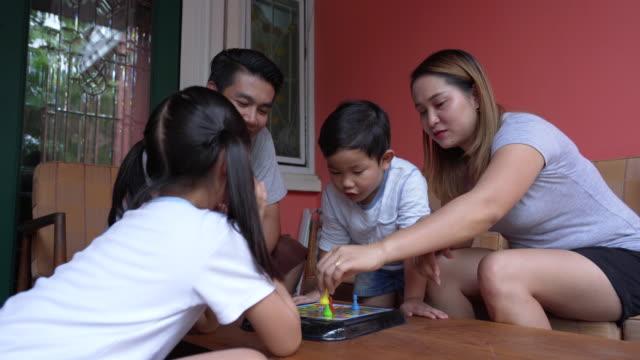 stockvideo's en b-roll-footage met aziatische familie lifestyle geniet van het spelen van het spel thuis - spelletjesavond