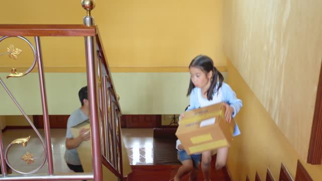 家に入る箱、段ボール箱に入るアジアの家族のライフスタイル、家を手配 - 余暇 ゲームナイト点の映像素材/bロール