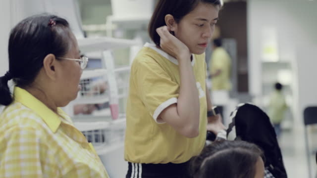 Asian family looking at a retail display of cabinet in a furniture store having fun