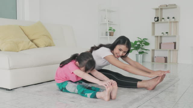 asian family mother and daughter doing yoga exercises in living room at home to maintain physical and mental health and wellbeing get exercise into your daily routine while social distancing. - two generation family stock videos & royalty-free footage