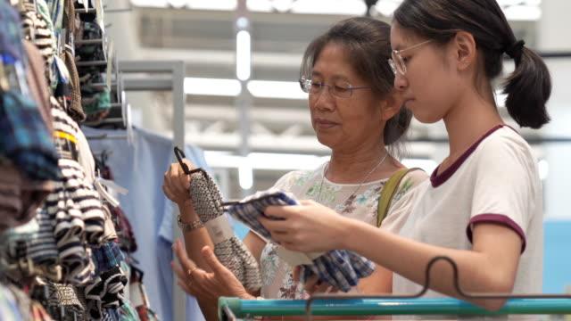 アジアの家族の母と十代の女の子は、販売店のショッピングモールで職業上のショッピングを楽しむ - 衣料品店点の映像素材/bロール