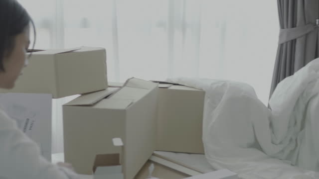アジアの家族の新しい家のボックスを移動 - 家の引っ越し点の映像素材/bロール
