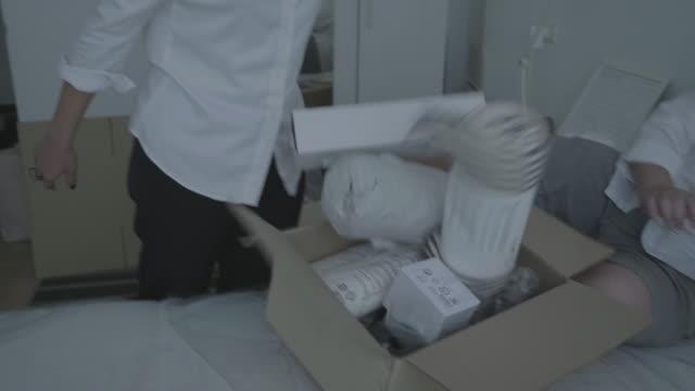 vídeos y material grabado en eventos de stock de casa asiática familia nueva mover cajas - pareja de mediana edad