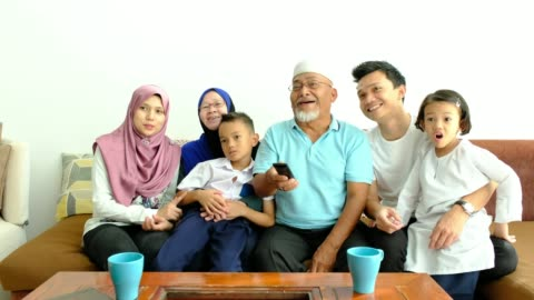 asian family on the couch watching tv - malaysian culture stock videos & royalty-free footage