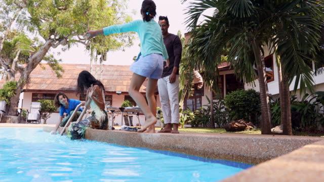 asiatischen familie auf urlaub in einem resort-pool plantschen - freibad stock-videos und b-roll-filmmaterial