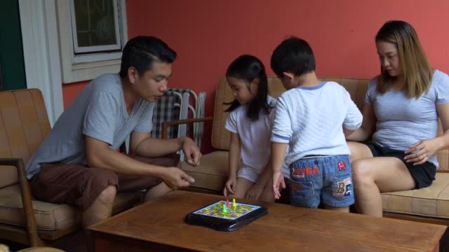 アジアの家族は自宅でダイスゲームをプレイ - 余暇 ゲームナイト点の映像素材/bロール