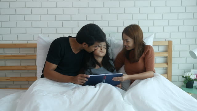 asian family reading book on bed - storytelling stock videos & royalty-free footage