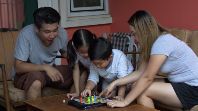 asian family relaxing indoors playing dice game at home - childhood stock videos & royalty-free footage