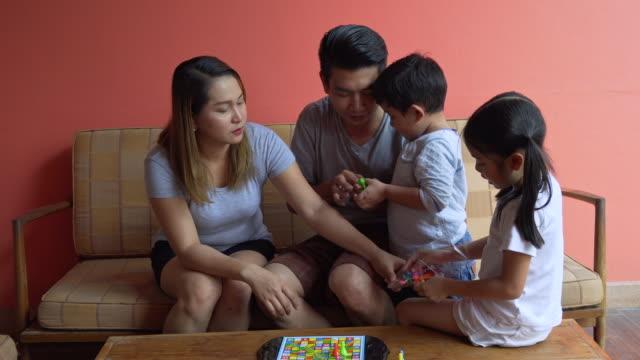 自宅でゲームをプレイアジアの家族リラックス屋内 - 余暇 ゲームナイト点の映像素材/bロール