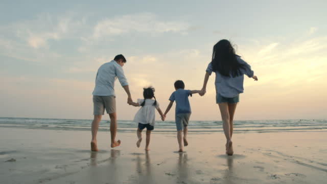 SLOW MOTION - Asian family running on the beach at sunset with happy emotion. Family, Holiday and Travel concept. Back Rear View.