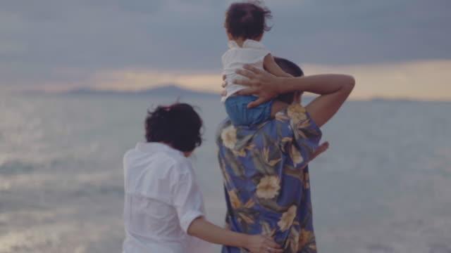 Asiatische Familie läuft am Strand bei Sonnenuntergang mit glücklichen Emotionen. Familie, Urlaub und Reisen
