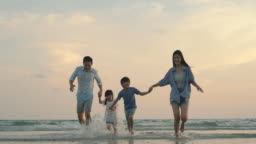Asian family running out of sea on summer vacation with happy emotion. Slow motion. Family, Holiday and Travel concept.