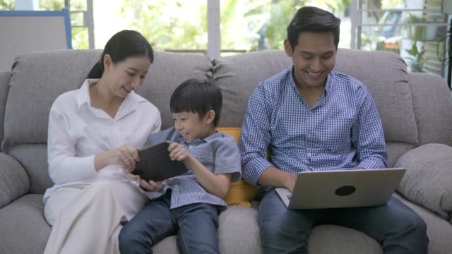 asian family sit in living room and play computor and tablet in weekend holiday. - baby boys stock videos & royalty-free footage
