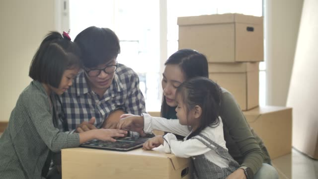 asian family sitting and using a tablet pc in their new home - over 80 stock videos and b-roll footage