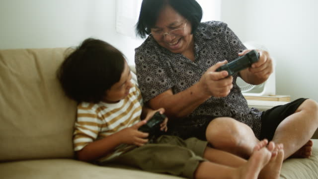 asian family sitting on couch playing video games - gamepad stock videos & royalty-free footage