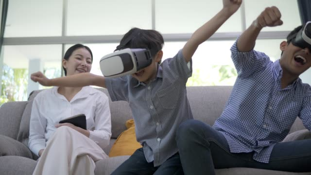vídeos de stock, filmes e b-roll de família asiática que usa o vr. ou realidade vertual em casa em férias de fim de semana. - realidade virtual