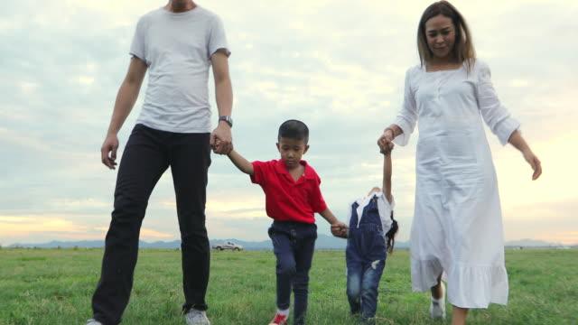 asiatische familie zu fuß und laufen auf der wiese bei sonnenuntergang mit glücklichen emotionen. familien-, urlaubs- und reisekonzept. - gemeinsam gehen stock-videos und b-roll-filmmaterial