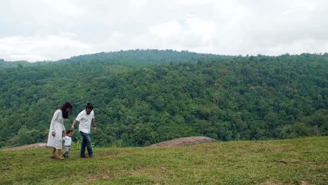 緑の丘の上を歩くアジア家族