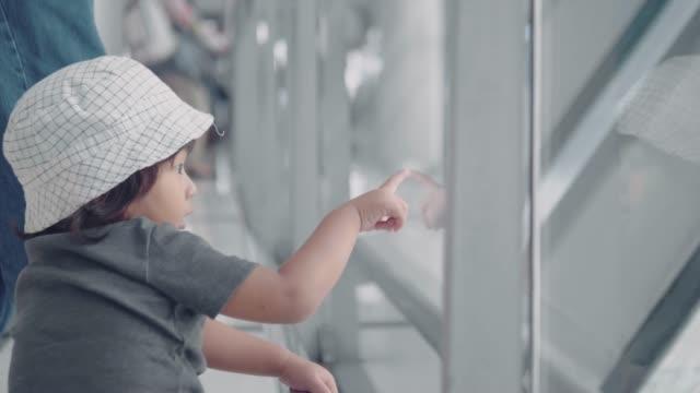 アジアの家族は空港で飛行機を見て - 玄関ホール点の映像素材/bロール