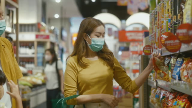 asian family wearing face mask and buying food at a supermarket. - freshness stock videos & royalty-free footage