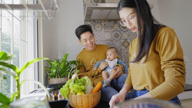 vidéos et rushes de famille asiatique avec un nouveau membre, bébé de cinq mois de fille passant le temps heureux ensemble pour préparer le petit déjeuner dans la cuisine, père retenant la fille pour regarder la mère faisant des sandwichs. - parents