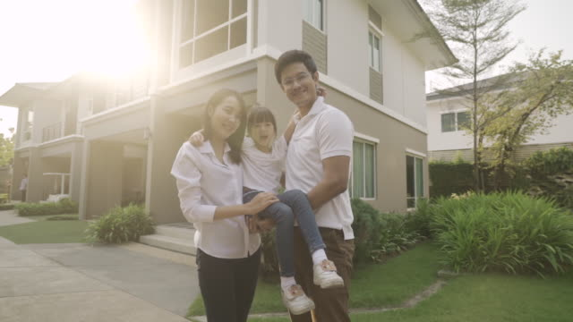 vídeos de stock e filmes b-roll de asian family with father and mother standing and carry daughter in front of their house look happy and smile. happiness and harmony in family life. - em frente de