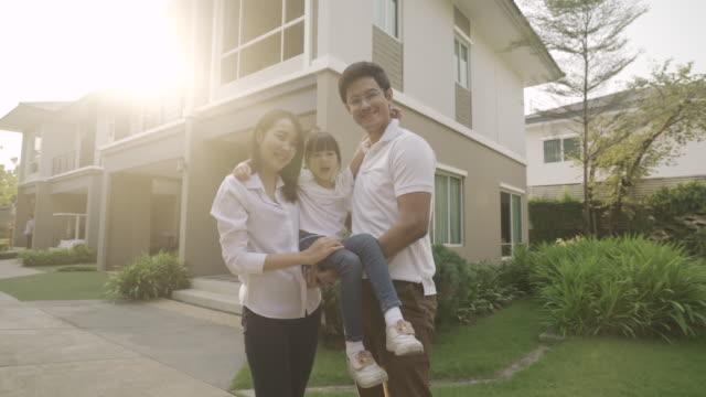 vídeos y material grabado en eventos de stock de familia asiática con padre y madre de pie y llevar hija frente a su casa se ven felices y sonríen. felicidad y armonía en la vida familiar. - delante de