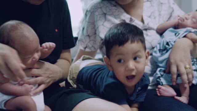 vidéos et rushes de famille asiatique avec des jumeaux sont assis dans le canapé. - frère