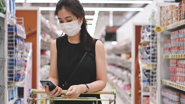 vidéos et rushes de famille asiatique femmes vérifier note de formulaire de liste en utilisant le téléphone intelligent faire payer avec qr code scan à payer au supermarché nouveau masque de style de vie normal - marchandise