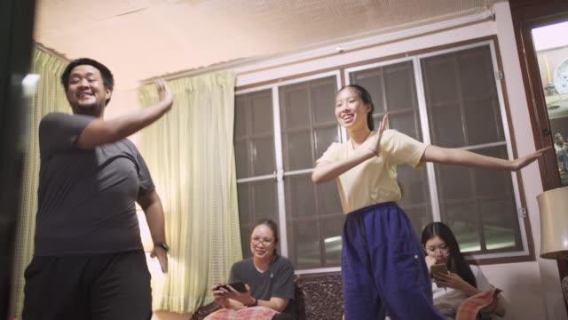 vídeos de stock, filmes e b-roll de família asiática de la malhando na sala de estar - treino esportivo